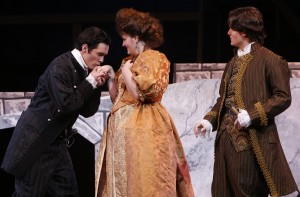 a male character kisses the hand of a female character while a second male character looks on