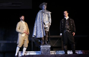 two male characters, flanking a statue